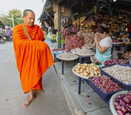 Sukhothai, Tahiland - 2019-03-06 - Monk Gives Blessing to Vendors in Exchange for Gifts of Food.