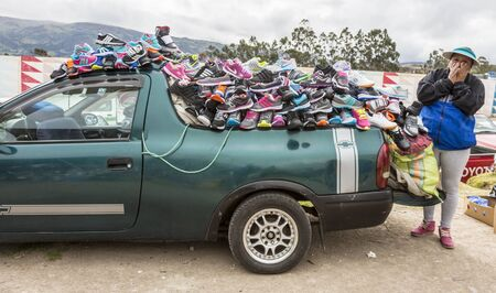 Canar, Ecuador - July 12, 2015 - A woman sells shoes out of the back of her car at the Saturday market