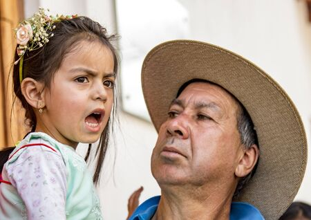 Cuenca, Ecuador Dec 24, 2017 - Father reacts to unhappy daughter, who is dressed for the annual Pase de Nino Christmas parade