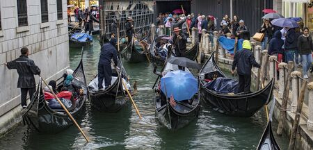 Venice, Italy - May 1, 2017: Gondolas are congested, yet try to work together to keep traffic flowing in the canals of Venice
