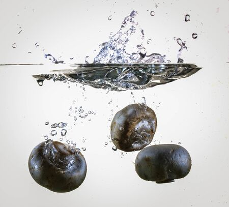 Blueberries dropping into water making a splash