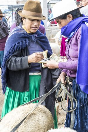 Canar, Ecuador - July 12, 2015 - A woman hands over cash to purchase sheep at the Saturday animal market