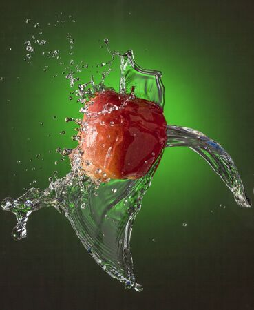 Water Splashes on Red Apple wet fruit throw Standard-Bild - 128585283