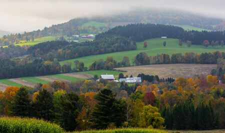 Rolling farm hills are broken by swaths of trees in full Autumn Color in Vermont Standard-Bild - 128473902