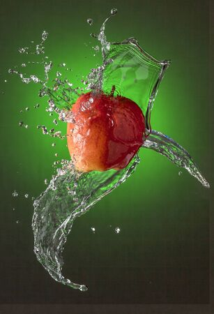 Water Splashes on Red Apple wet fruit throw Stock Photo