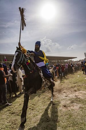PUNJAB, INDIA, MARCH 2, 2018: Hola Mohalla Festival - Man on horse at full gallop holds his tufts at the end of his spear high, showing his tropies