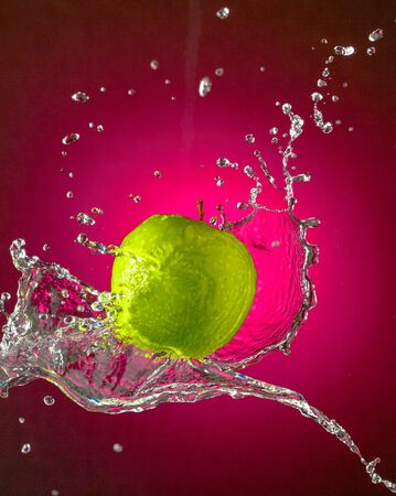 Water Splashes on Green Apple wet fruit throw Stock Photo - 128361735