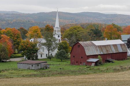 A small church sits on a farm next to a weathered red barn during Autumn in Vermont Standard-Bild - 128584283