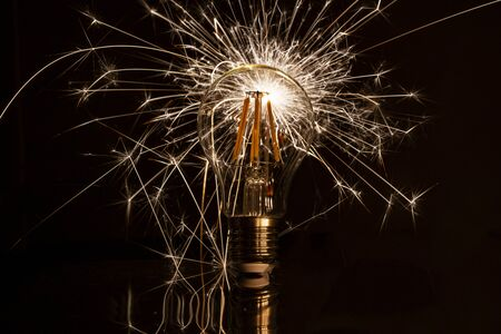 Fireworks sparkler behind LED light bulb burns Standard-Bild - 128584774
