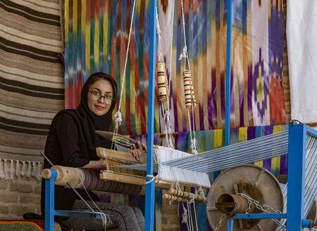 Isfahan, Irán - 2019-04-12 - Mujer teje tela en un telar manual. Editorial