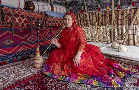 Shiraz, Iran - 2019-04-09 - Qashgal woman smokes water pipe hookah in her tent.