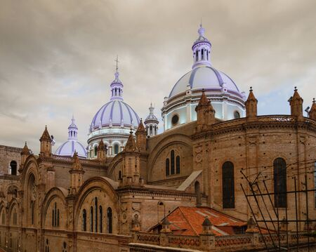 Famous domes of the New Cathedral in Cuenca, Ecuador rise over the city skyline.