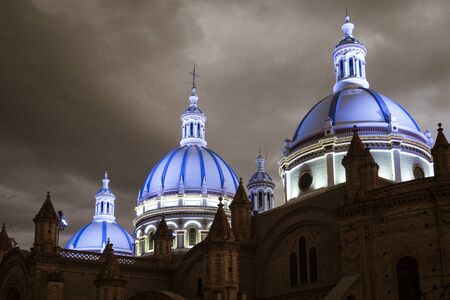 Famous domes of the New Cathedral in Cuenca, Ecuador rise over the city skyline at dusk.