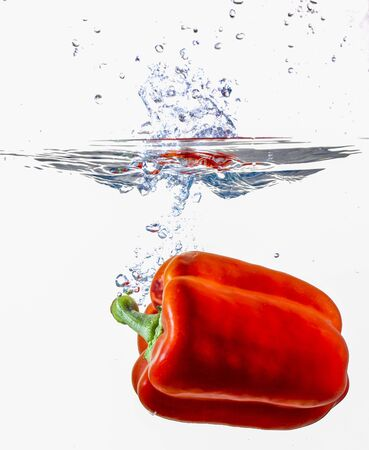 Red Bell Pepper Dropping Into Water making a splash Imagens
