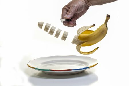 Slicing up breakfast - A human hand holding a knife and slicing a half peeled banana with the slices suspended midair over a plate Imagens