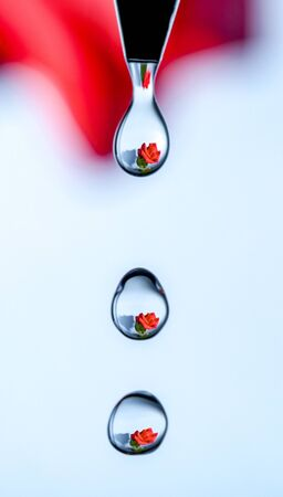 A rose caught reflected in a series of drips of water from a faucet