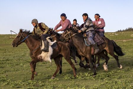 Issyk Kul, Kyrgyzstan - May 28, 2017 - Buzkashi players race towards the goal with their headless goat