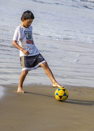 Puerto Lopez, Ecuador - August 19, 2016 - Boy plays soccer futbol on the beach Editorial