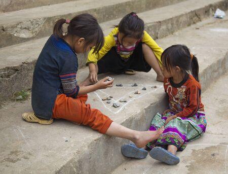 Sapa, Vietnam - Oct 22, 2011: Three girls play a game on school steps Editorial
