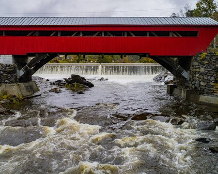 A red covered bridge first built in 1883 spans a rapidly flowing river with small hydroelectric plant dam in Vermont 免版税图像