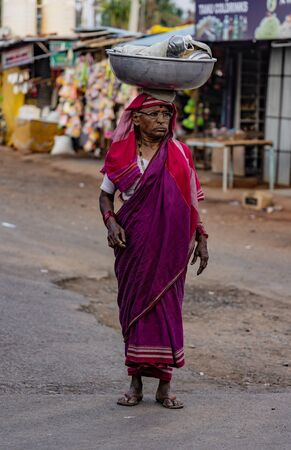 BADAMI, INDIA, MAR 18, 2018: Woman carries her load on her head