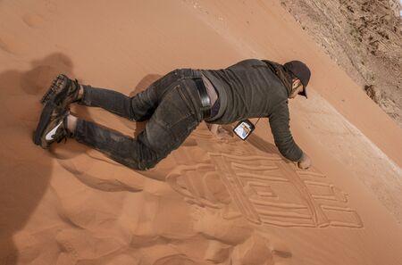 Wadi Rum, Jordan - 2019-04-23 - Man draws intricate patterns in the sand dune. Editoriali