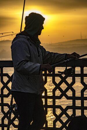 Istanbul, Turkey - April 1, 2016 - Man fishes off the bridge at sundown Editoriali