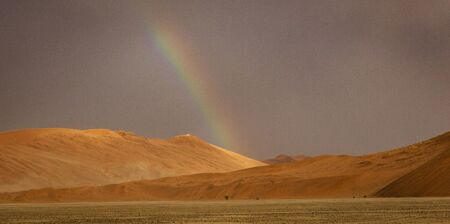 Rainbow shines over a sand dune in the desert in Namibia Reklamní fotografie
