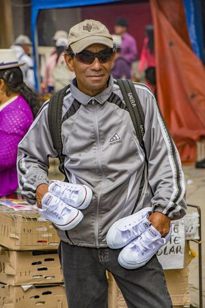Cuenca, Ecuador - August 24, 2017 - Man selling tennis shoes on the street, showing them off on his hands