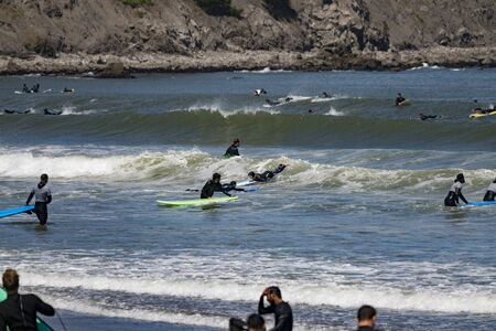 Pacifica, California - June 16, 2018: Surfers and paddle-boards compete for the few waves on this beach in California Editoriali