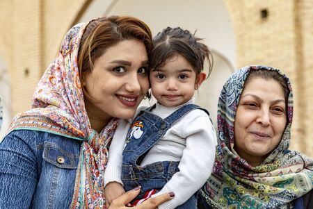 Kashan, Iran - 2019-04-14 - Naqshe Cehan Square three generations pose for the foreign photographer. Editoriali