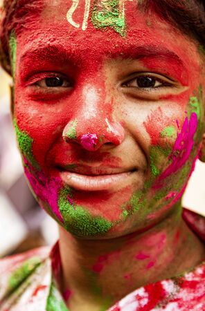 Barsana, India, Holi Festival, Feb 24, 2018 - Boy smiles at camera covered in paint during Holi Festival in India