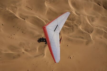 Walvis Bay, Namibia - July 16, 2018: An ultralight aircraft is seen flying with sand dunes as a backdrop in Namibia
