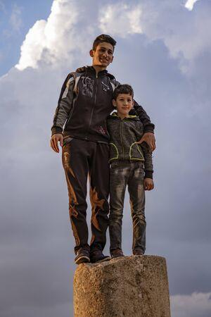 Jerash, Jordan - 2019-04-19 - Two boys stand on a pillar from a 2000 year old Roman ruin. Editoriali