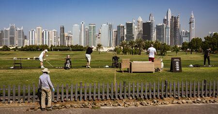 DUBAI, UAE, MAR 20, 2018: Golfers practice on driving range with Dubai skyline in the background