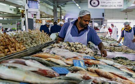 ABU DHABI, UAE, MAR 22, 2018: Man prepares fish for sale at the largest fish market in Abu Dhabi