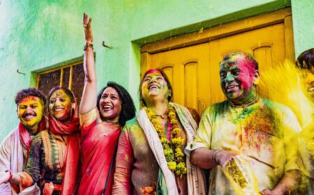 Barsana, India - February 23, 2018 - Indian family laughs while throwing powdered paint into the air during Holi festival
