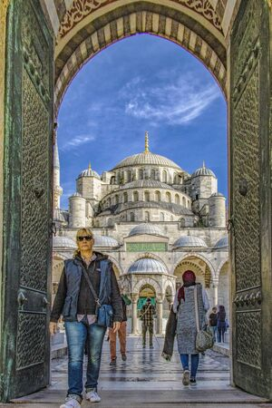 Istanbul, Turkey - April 1, 2016 - Woman walks out through doors of the Blue Mosque Editoriali
