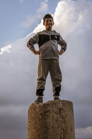 Jerash, Jordan - 2019-04-19 - A boy stands on a pillar from a 2000 year old Roman ruin.