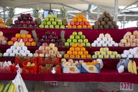 Tashkent, Uzbekistan - May 18, 2017 - Fruit stand shows apples, oranges and other produce in neatly stacked piles