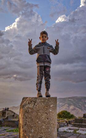 Jerash, Jordan - 2019-04-19 - Boy stands on a pillar from a 2000 year old Roman ruin. Editoriali