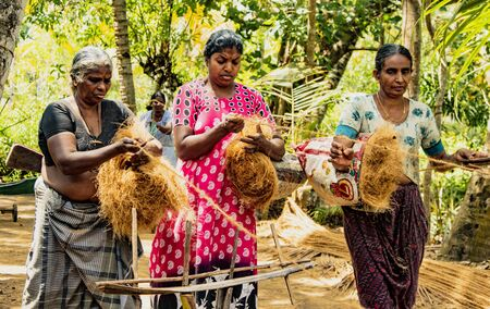 MONROE ISLAND, INDIA, MAR 15, 2018: Women spin coconut hair by hand, turning it into a strong rope