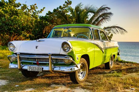 Trinidad, Cuba, Nov 28, 2017 - Green and white 1950 s Class America  Ford Fairlane parked on beach