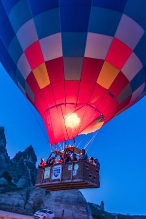 Goreme, Turkey - April 6, 2016 - Pilot fires the heater in his hot air balloon as he prepares it for flight
