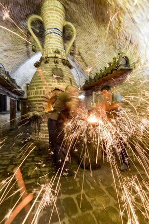 Bukhara, Uzbekistan - May 22, 2017 - Two blacksmiths use hammers to beat hot metal as sparks fly Editoriali