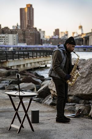BROOKLYN, NEW YORK, MAR 27, 2018: Man plays saxophone for donations in Dumbo Park
