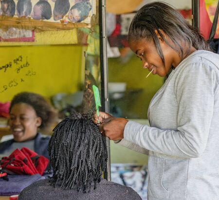 Windhoek, South Africa - July 6, 2018: A hair stylist works on a client s hair in a tiny shop in Namibia Editoriali