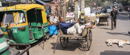 New Delhi, India - February 19, 2018 - Man Rests In His Wooden Cart While Waiting For Next Job