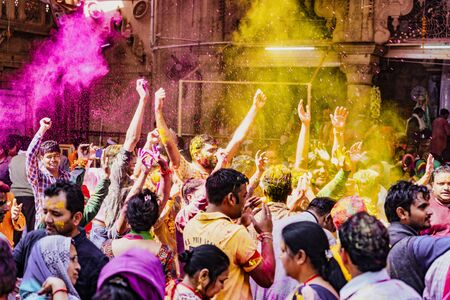 Barsana, India - February 23, 2018 - The crowd erupts in laughter and dance as powdered paint is thrown in the air during Holi festival
