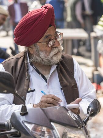 New Delhi, India - February 19, 2018 - Man With Grey Beard and Turban Writes In His Notebook While Talking To Person Off Screen Editoriali